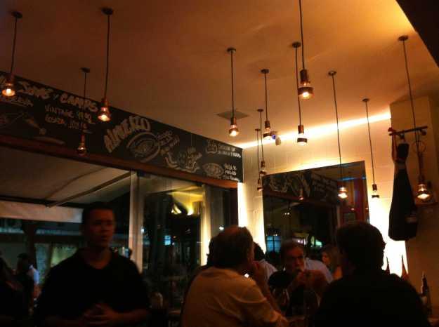 Luminárias simpáticas descem do teto mantendo o clima intimista do pequeno salão do Venga.. Detalhe para o quadro negro..