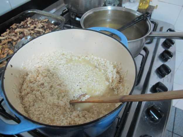 Caldo aquecido ao lado e o arroz em seu início... Foi secando vai juntando caldo sempre aos poucos... Risoto é um prato que demanda paciência..