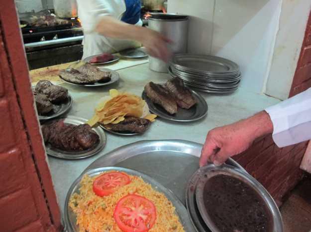 A cozinha é funcional e os pedidos voam... Repare no tamanho cada vez menor das peças de carne, principalmente do mignon...