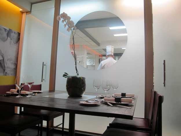 Pela janela você acompanha o ballet da cozinha.. Ao lado o detalhe do painel com momentos da vida de Roberta Sudbrack e a decoração minimalista..
