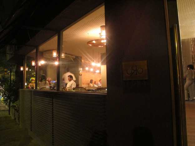 Fachada discreta na rua Frei Leandro, no Jardim Botânico.. Ao fundo, o chef na mesa de amigos...