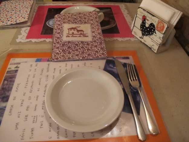 A mesa com jogo americano feito pela própria casa, sem padrão.. O cardápio com capa de pano...