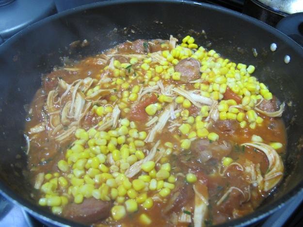 Após mexer bem e apurar o sabor dos tomates, entre com o que falta: as ervas, o milho e o frango desfiado..