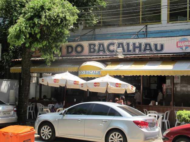 A fachada do restaurante que dá de frente para a pracinha.. Mesas na varanda, balcão e salão..