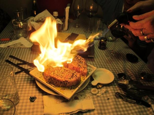 A finalização ocorre na mesa com um maçarico.. É importante ter cuidado por causa da gordura do azeite!