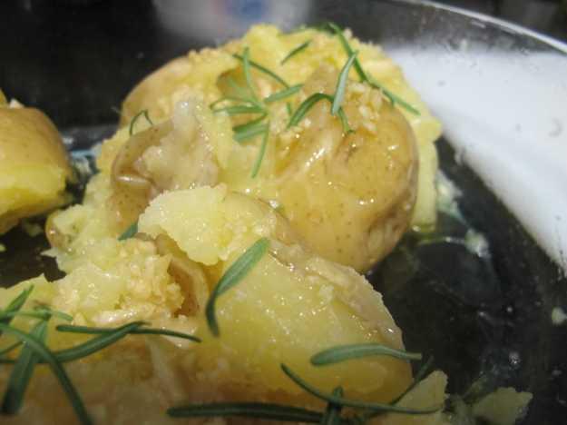 Após esmurrar as batatas, entre com o alho misturado com o azeite, e o alecrim.. Depois é só ir ao forno!